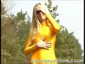 Hot babe looking like a crazy yellow human reptile in her shiny yellow spandex suit and with her cat-like green eyes.