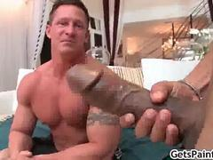Mature muscle bound guy enjoys sucking a huge black cock