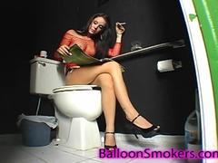 Busty Bonnie smoking a cigarette while sitting in a bathroom